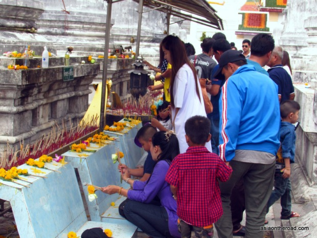 fedeli donano fiori e incenso